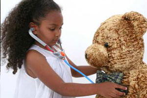 Girl listening to teddy bears heart